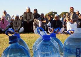 Muslims site before bottles of water